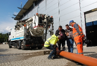 people in workwaer standing in front of sewer cleaning vehicle