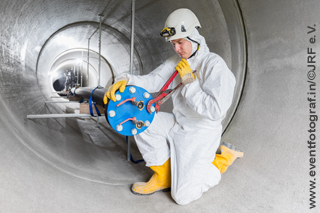 man in white overall with yellow helmet working on pressure sewer pipe test rig
