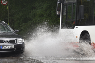 car and bus on flooded road, water splashing