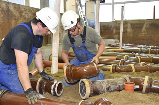 two men installing sewer pipes in testing facility