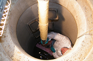 man in manhole installing short liner