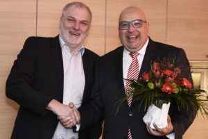 two men in suits shaking hands, one holding flower bouquet