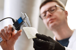 man with black glove measuring wall thickness of liner sample