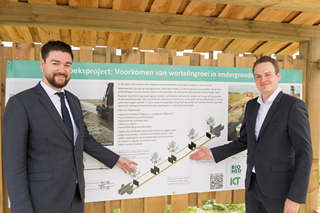 two men in suits pointing at information board