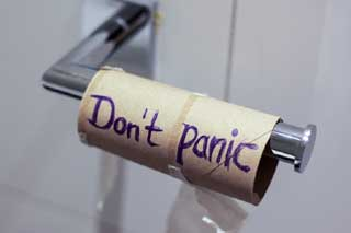 empty toilet paper roll with the word don't panic written on it