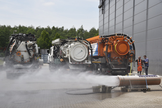 water spraying from pipe in front of three sewer cleaning vehicles