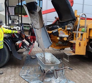 flowable backfill flowing from mixing truck into wheelbarrow