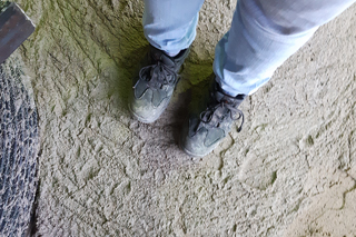 person with work shoes standing on hardened flowable backfill